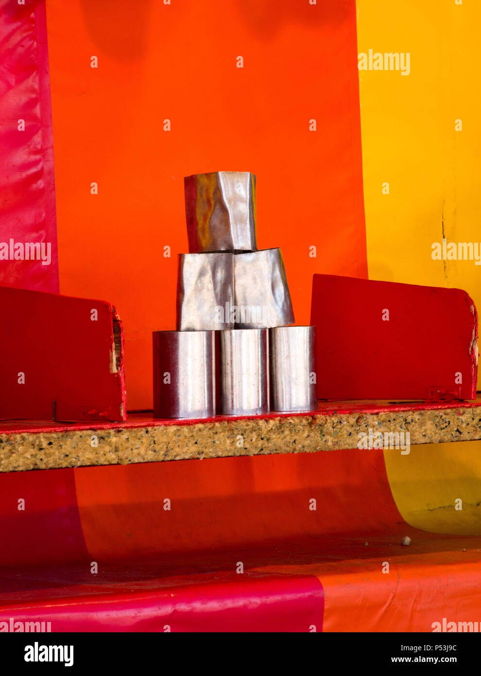 fun fair / amusement game of tin can alley where competitors have to knock all cans off the shelf to win a prize - Stock Image