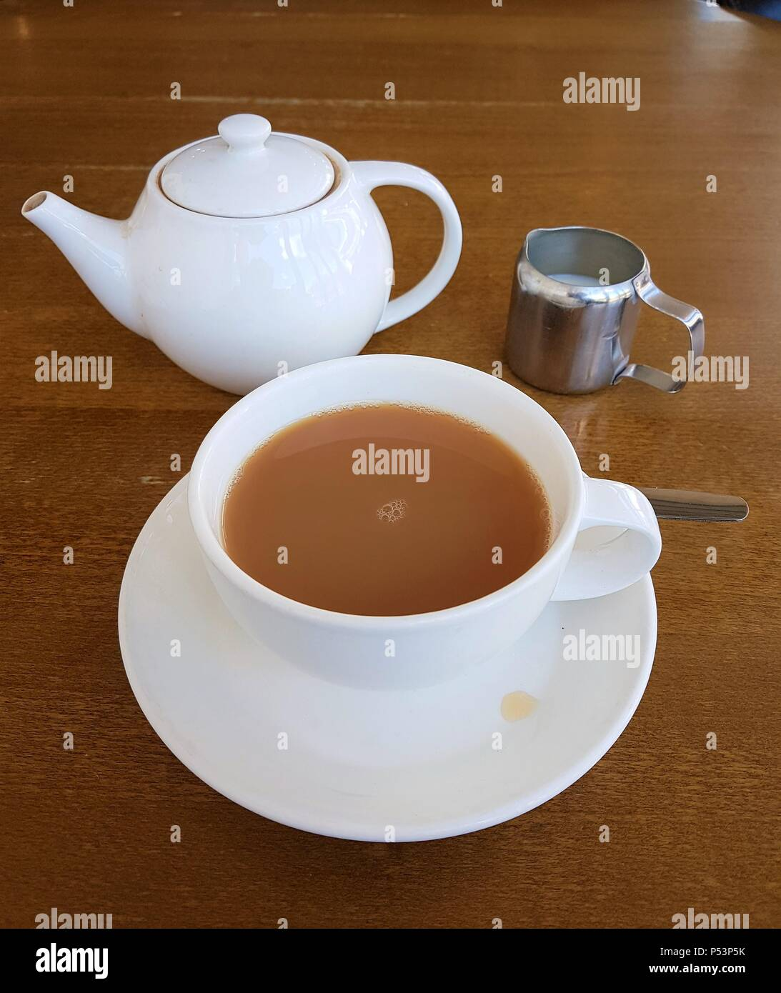 Tea cup filled with tea on saucer with tea pot and milk on a table - Stock Image