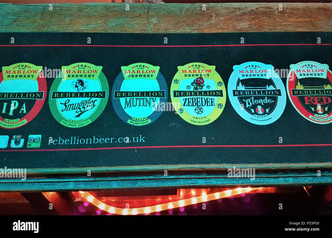 The Marlow Brewery / Rebellion Beer Company bar drip rubber mat on a bar displaying Rebellions beer Stock Photo