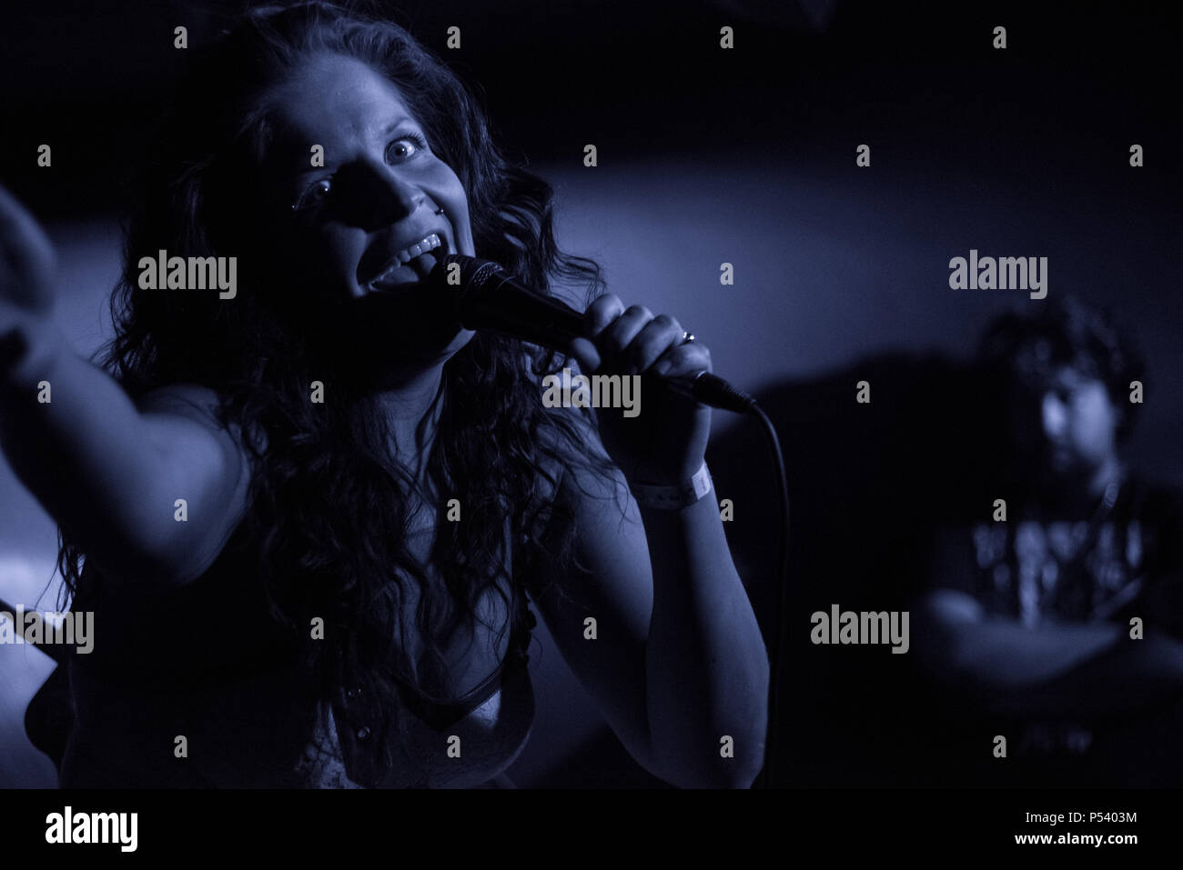 Suvi Uura, Lead singer of the Finnish metal band Dorothy Polonium, on stage Looking at the camera in low key bluish light - Stock Image