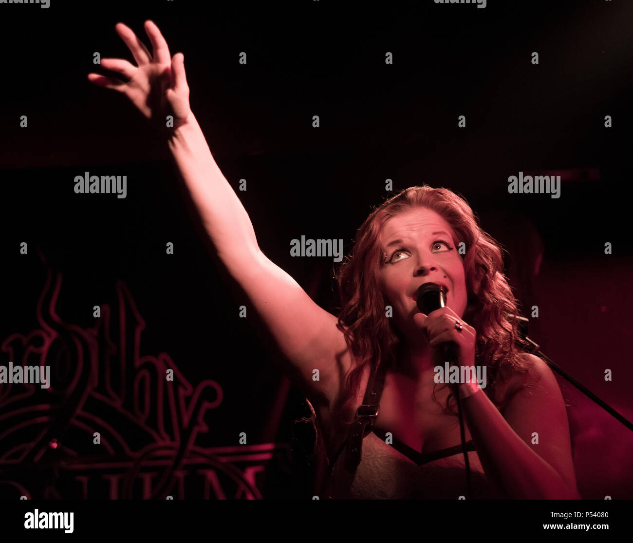 Suvi Uura, Lead singer of the Finnish metal band Dorothy Polonium, on stage with hand up in the air with eyes looking up - Stock Image