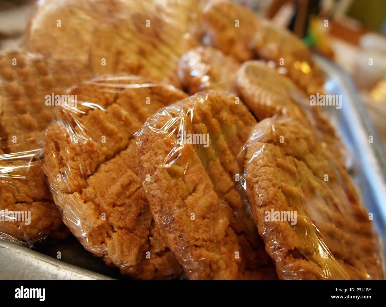 Freshly baked peanut butter cookies in plastic wrap at a coffeehouse bakery counter. - Stock Image