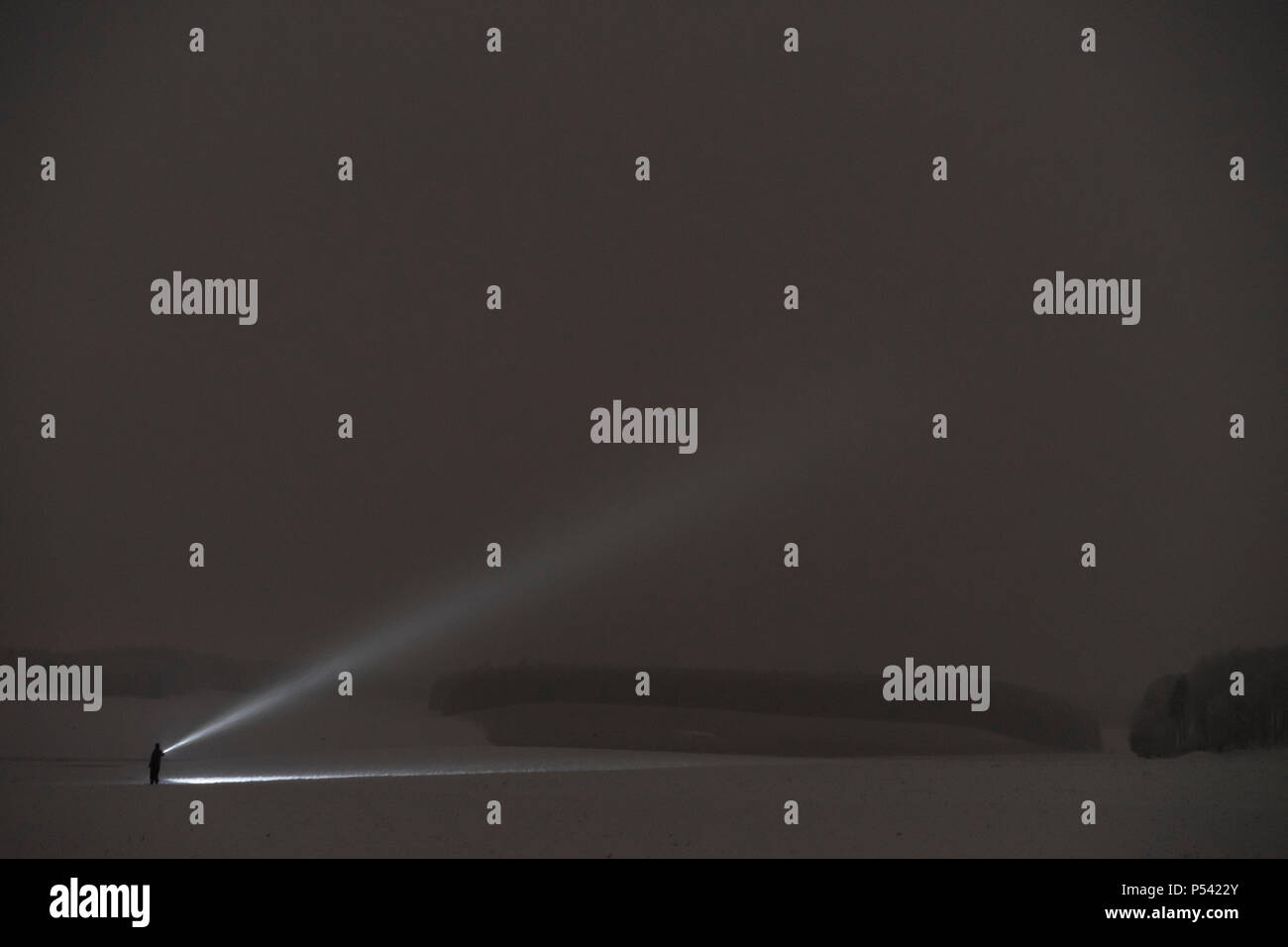 Human shining with flashlight at night in Sweden Scandinavia Europe. Dark abstract and mystical picture of man with torch. - Stock Image