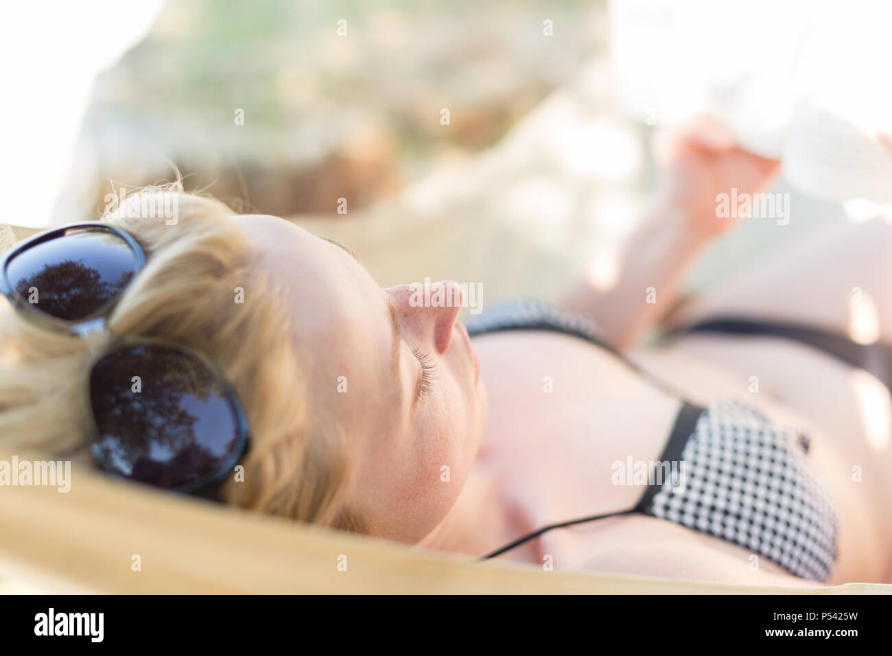 Woman reading book in hammock on the beach - Stock Image