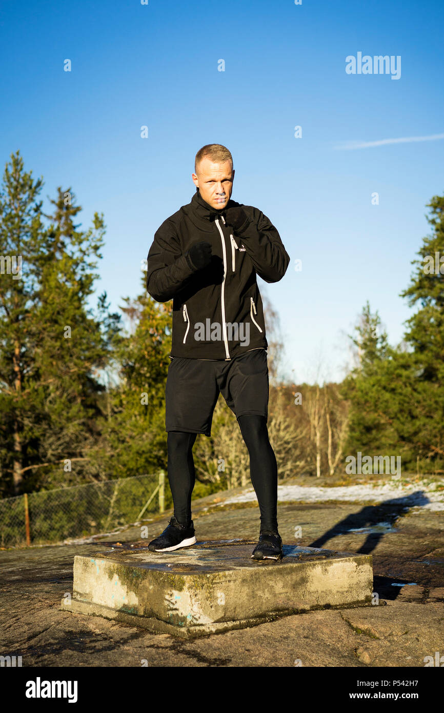 Male caucasian middle age boxer training outside in nature. Nice sunny winter day in the forest with blue sky. Wearing black sport clothes - Stock Image