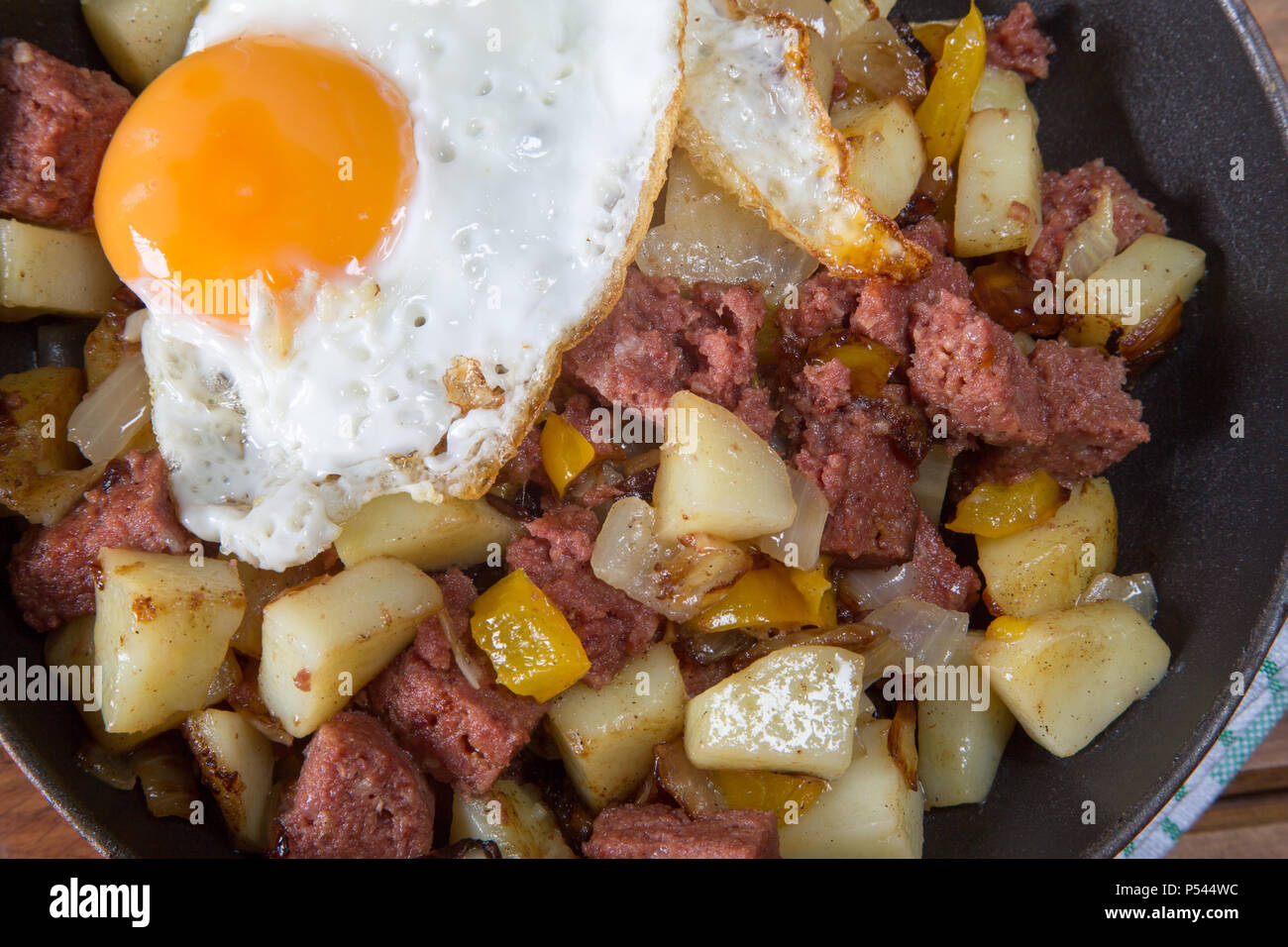 Freshly cooked Corned beef hash with a fried egg served in the pan. - Stock Image