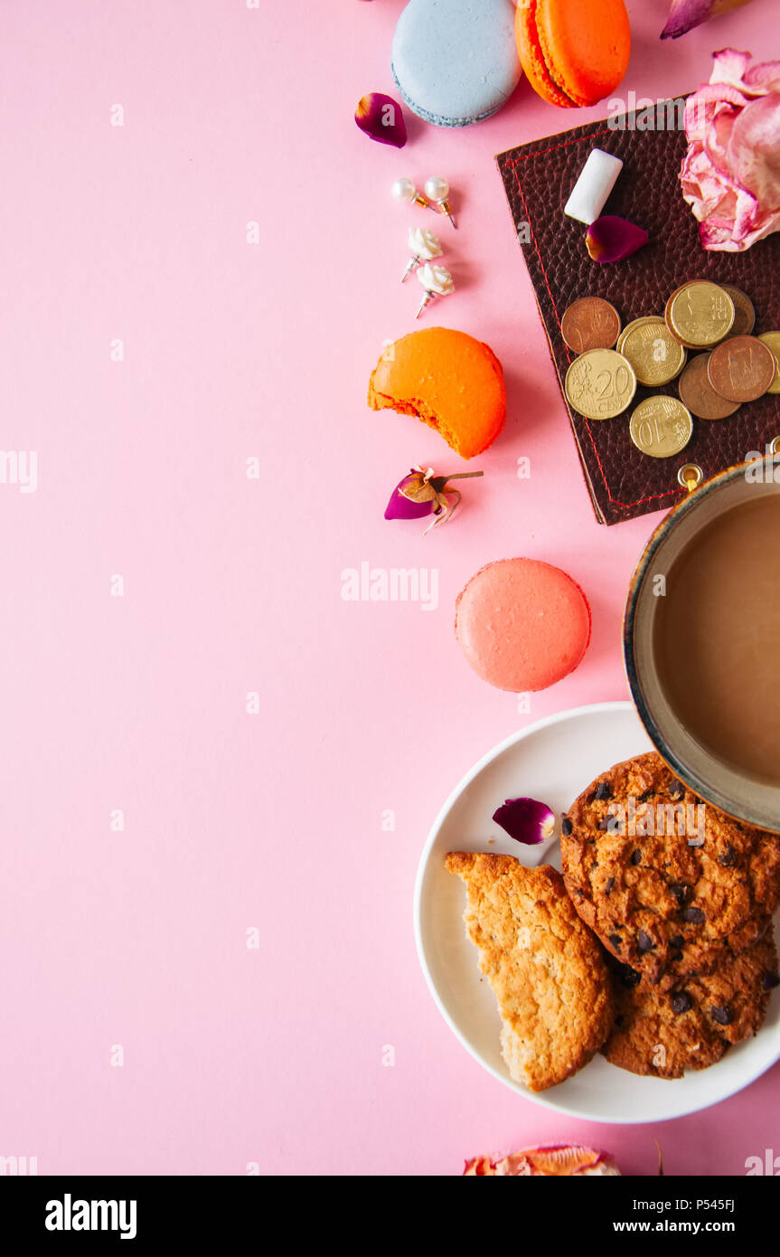Flat lay of femenine things cookies coffee pearls flowers on a pknk background. Top view. Stock Photo