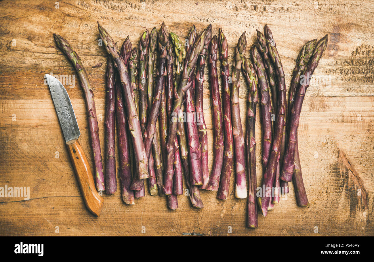 Fresh purple asparagus over wooden background - Stock Image