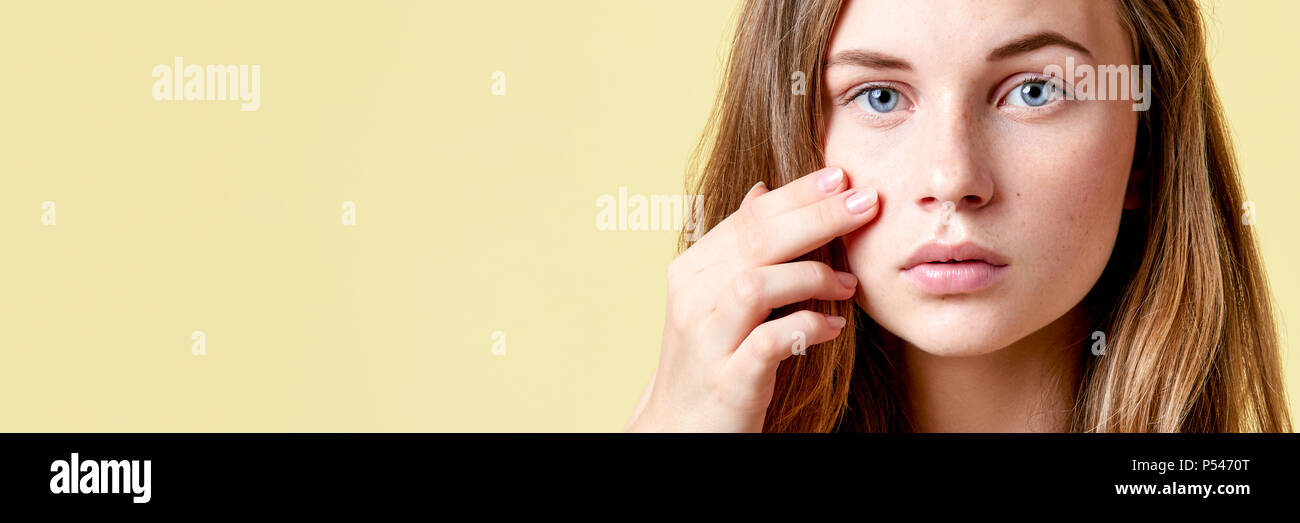 Young redhead teenager with self issues looking into mirror. Girl with low self esteem checking her skin in a mirror banner. - Stock Image