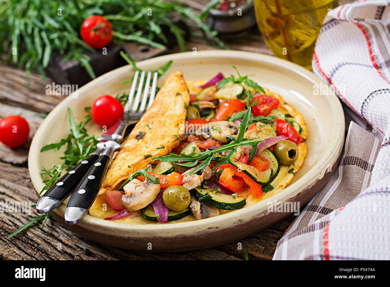 Omelet with tomatoes, zucchini and mushrooms. Omelette breakfast. Healthy food. - Stock Image