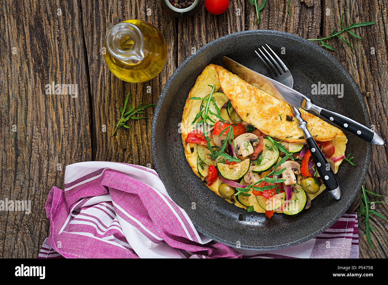 Omelet with tomatoes, zucchini and mushrooms. Omelette breakfast. Healthy food. Top view. Flat lay - Stock Image