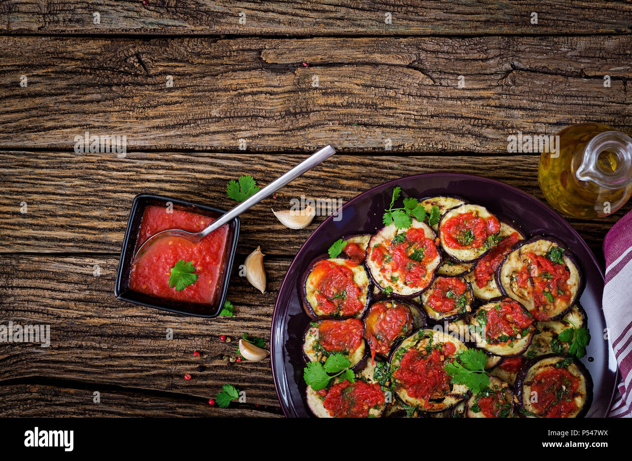 Eggplant grilled with tomato sauce, garlic, cilantro and mint. Vegan food. Grilled aubergine. Top view. Flat lay - Stock Image