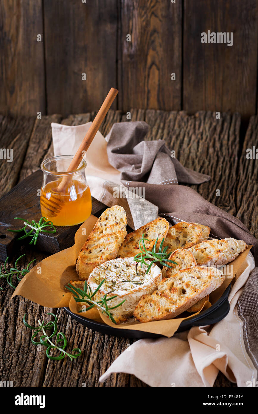 Baked cheese Camembert with rosemary and honey. Tasty food. - Stock Image