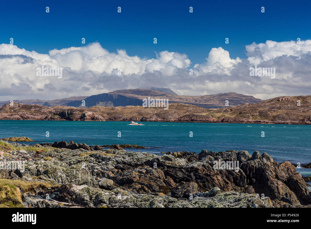 A colourful ferry crosses the Sound of Iona with the mountains of Mull and Ben More beyond, Argyll and Bute, Scotland, UK - Stock Image