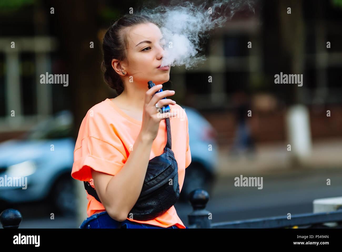 Pretty young girl vape popular ecig gadget,vaping device.Happy brunette vaper girl with e-cig.Portrait of smoker female model with electronic cigarett - Stock Image