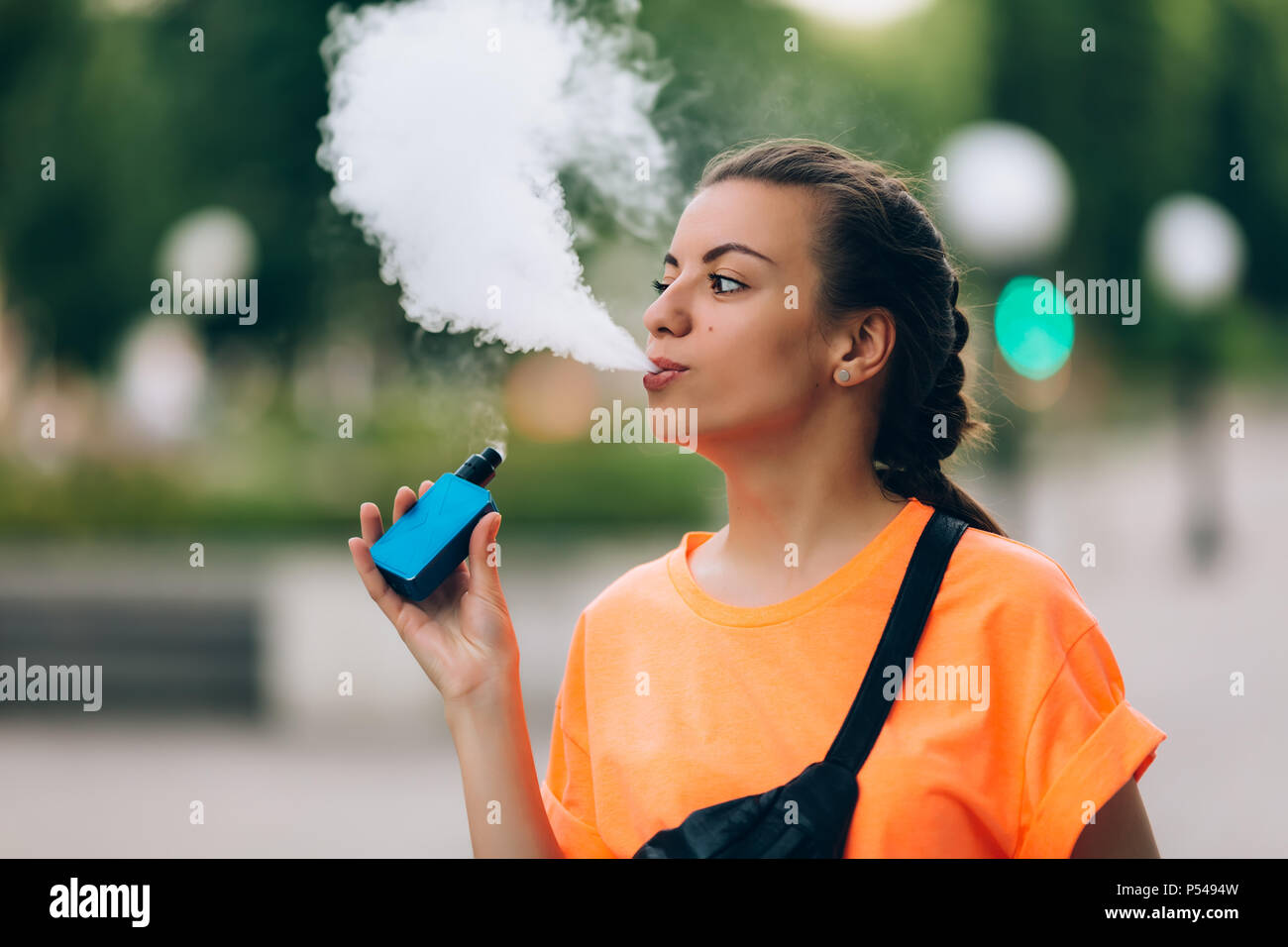 Pretty young girl vape popular ecig gadget,vaping device.Happy brunette vaper girl with e-cig.Portrait of smoker female model with electronic cigarett - Stock Image