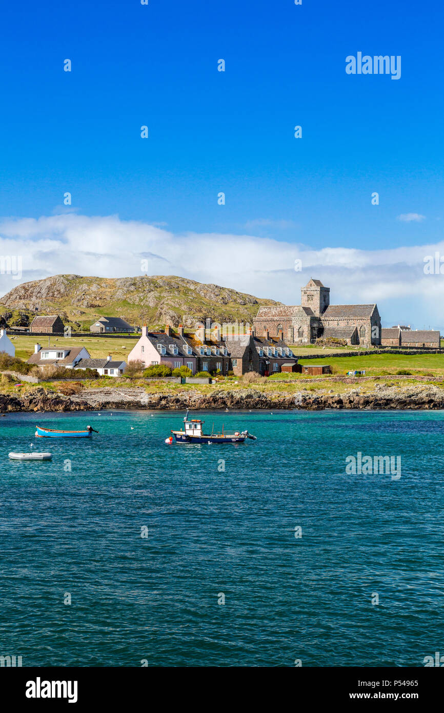 A collection of small fishing boats at Baile Mor together with the abbey church  on the Hebridean island of Iona, Argyll and Bute, Scotland, UK - Stock Image