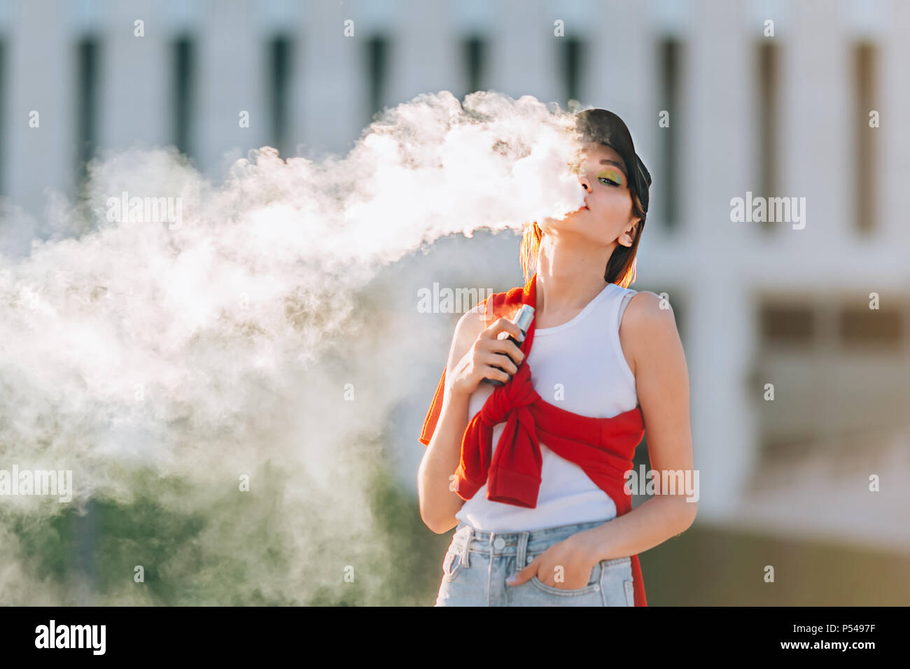 Pretty young asian girl vape popular ecig gadget,vaping device.Happy brunette vaper girl with e-cig.Portrait of smoker female model with electronic ci - Stock Image
