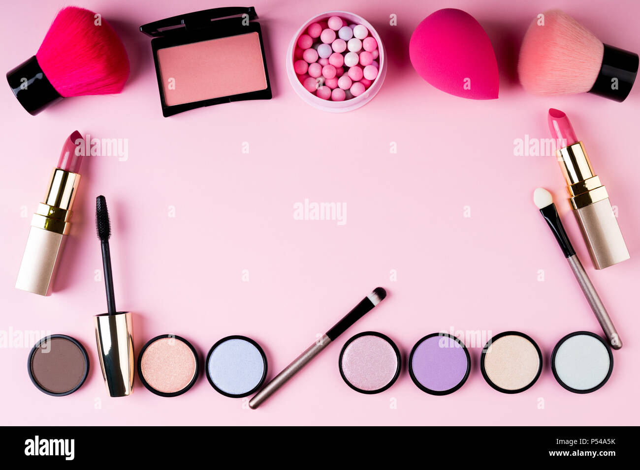 Frame of makeup products and decorative cosmetics on pink