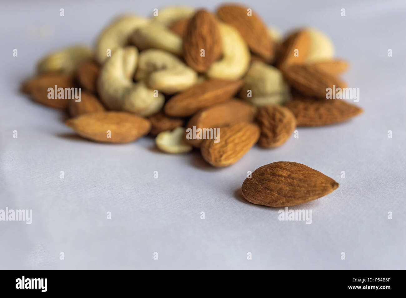 An almond isolated from a heap of other nuts like almonds and cashew - Stock Image