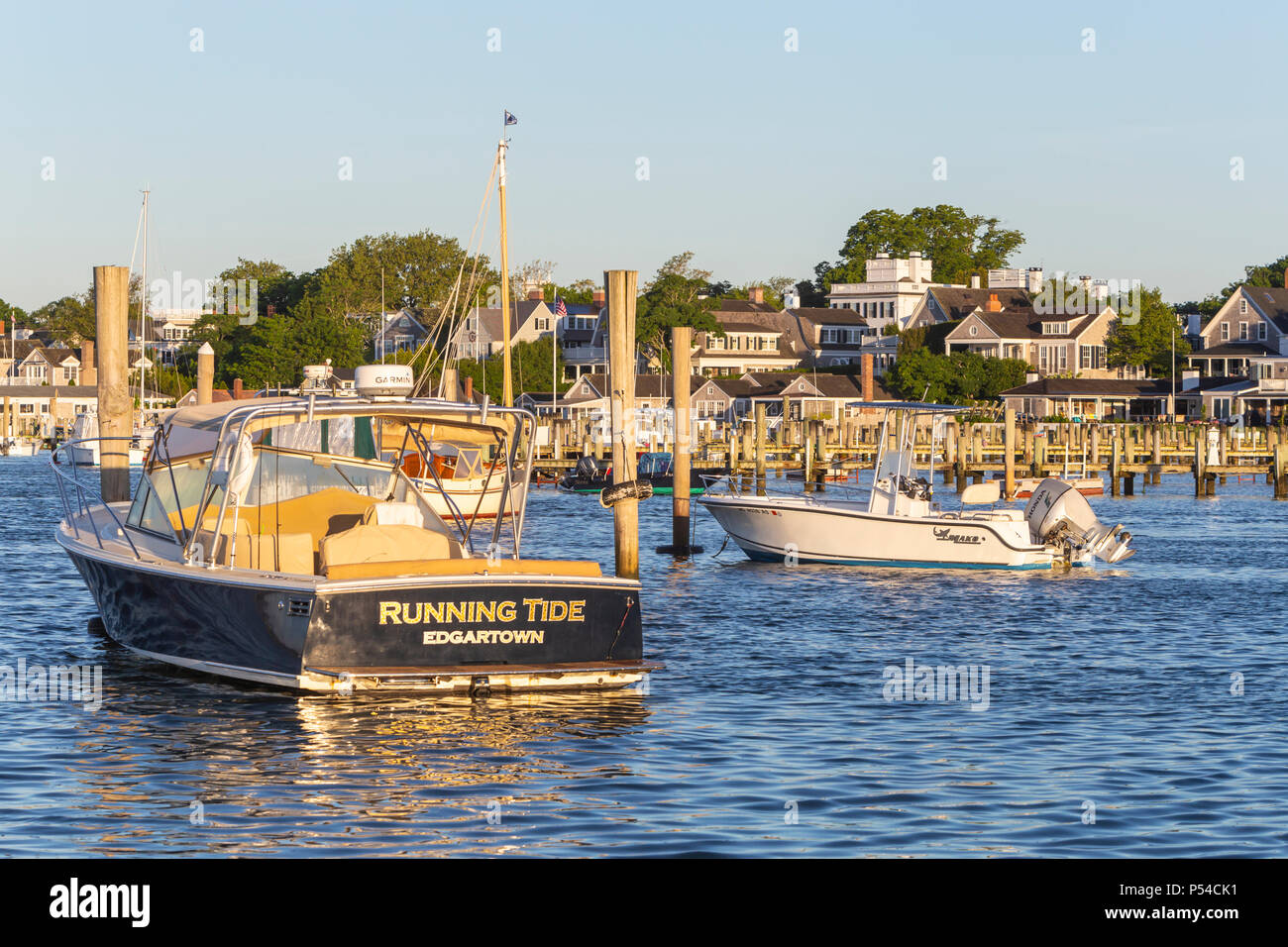 Boats moored and docked in the harbor, overlooked by stately sea captains' homes in Edgartown, Massachusetts on Martha's Vineyard. - Stock Image