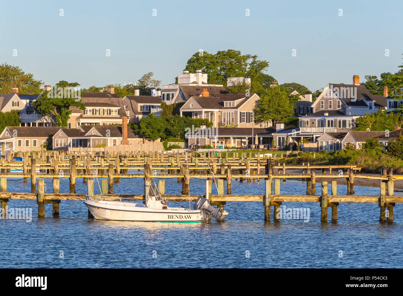 A boat docked in the harbor, overlooked by stately sea captains' homes in Edgartown, Massachusetts on Martha's Vineyard. - Stock Image