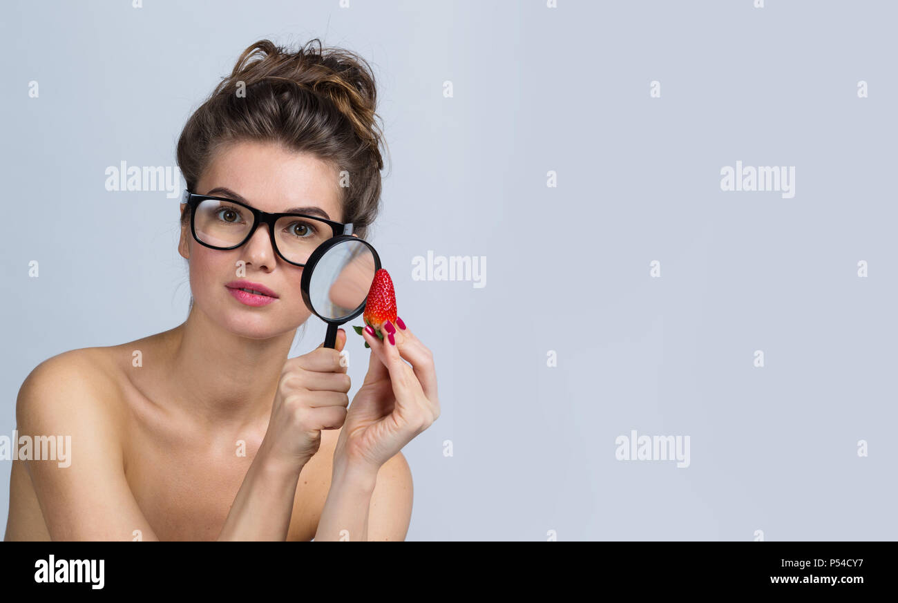 Funny woman in glasses holding strawberry and look at it through magnifying glass investigating quality and usefulness - Stock Image