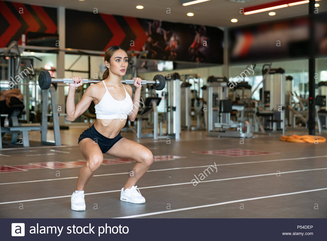 Close Up of young fitness woman executed exercise with exercise-machine Cable Crossover in gym. - Stock Image