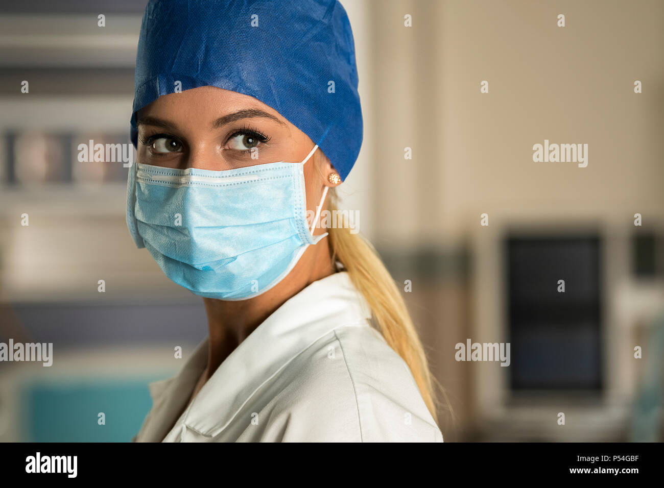Blonde young nurse doctor in ICU ER OR room - Stock Image