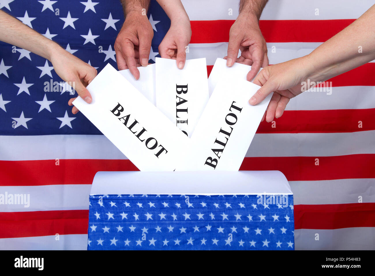 hands placing ballots in a voting box, American flag in background. Anyone over the age of 18 on election day and a citizen of the United States is el - Stock Image