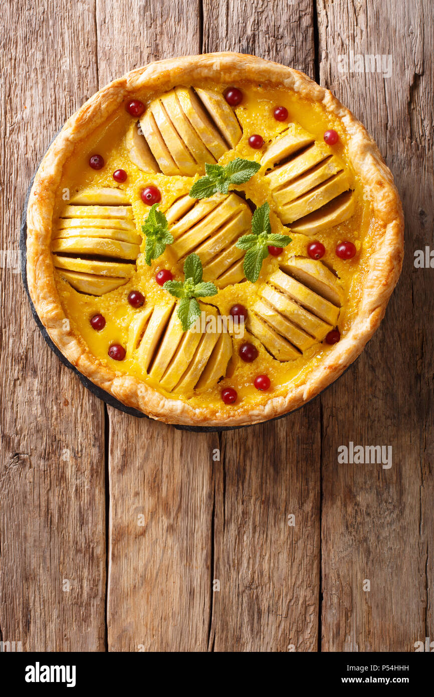 Freshly baked apple pie with cranberries, custard and mint closeup on the table. Vertical top view from above - Stock Image