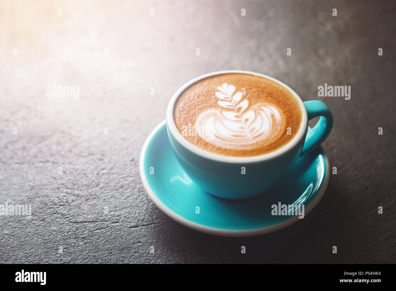 A cup of cappuccino with beautiful latte art on stone table. Morning mood concept. - Stock Image