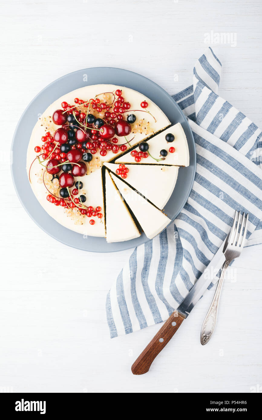 Homemade cheese cake with berries on white wooden table with towel, knife and fork. Top view. Red currant, black currant and cherry. - Stock Image