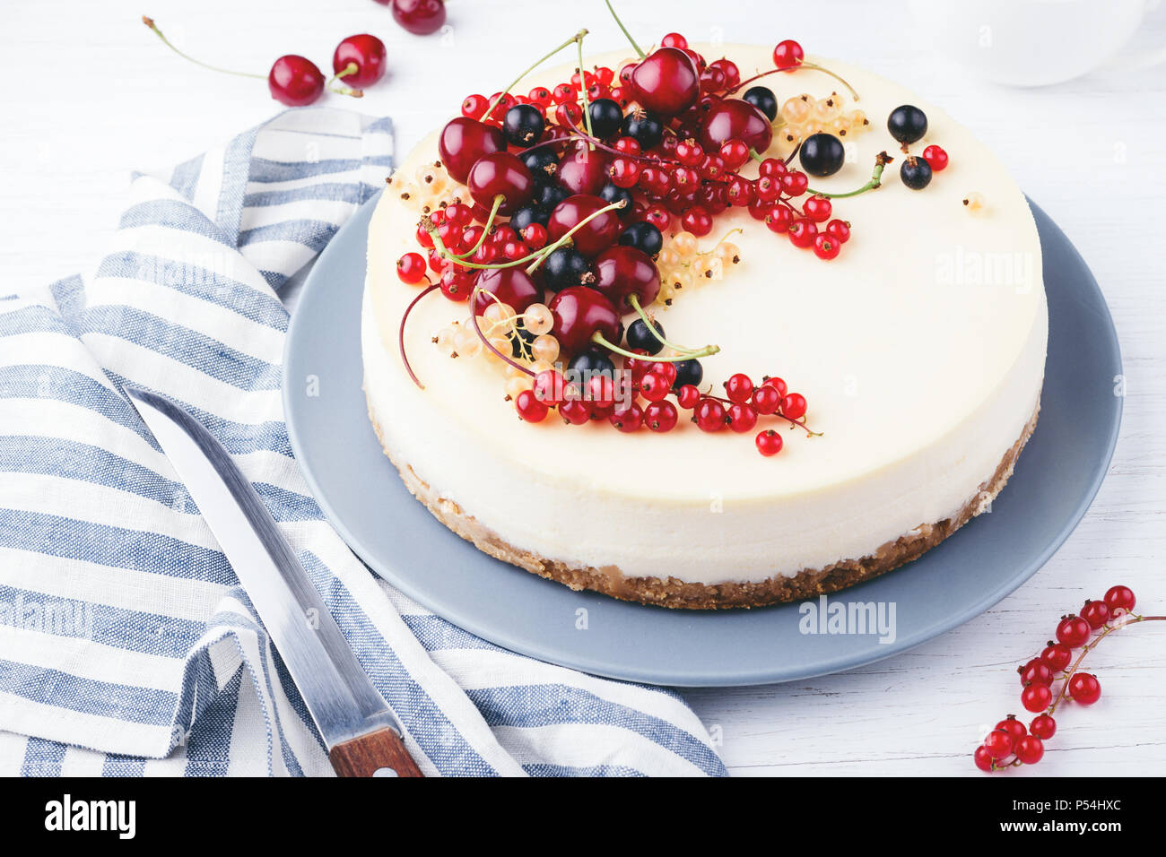 New York cheese cake with berries on white wooden table. Angle view. Stock Photo