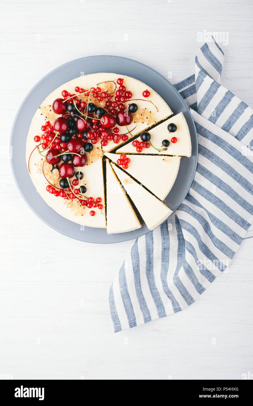New York cheese cake with berries on white wooden table. Top view. Red currant, black currant and cherry. - Stock Image