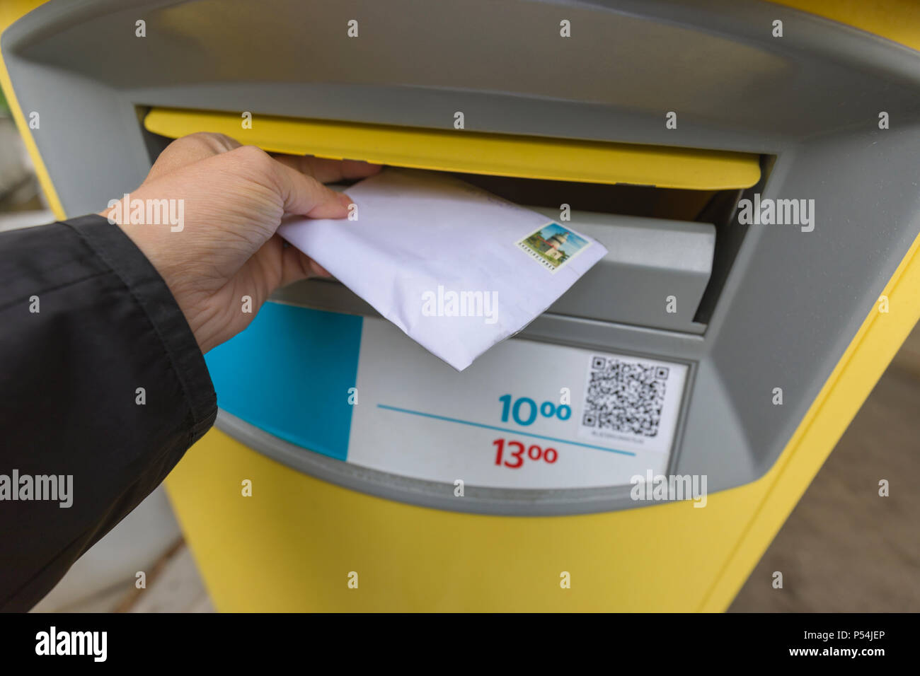 Man posting off a a letter in a post or mail box - Stock Image