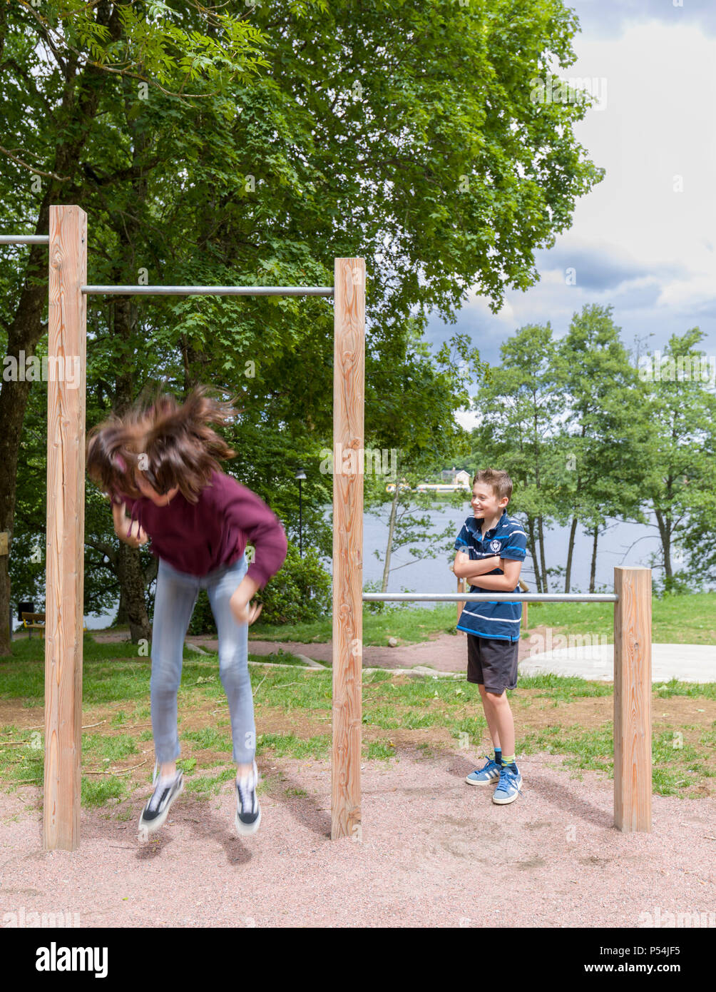 Teenage girl jumping off a crossbar in playpark whilst younger brother watching in awe - Stock Image