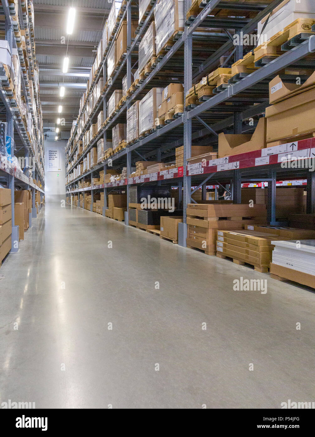 Interior view of aisles in a large warehouse stacked with cardboard boxes - Stock Image