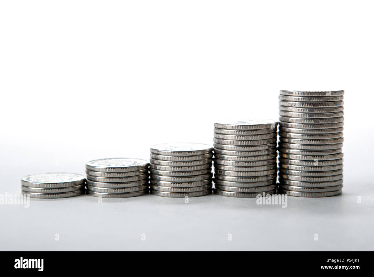stacks of coins on a white background close up - Stock Image