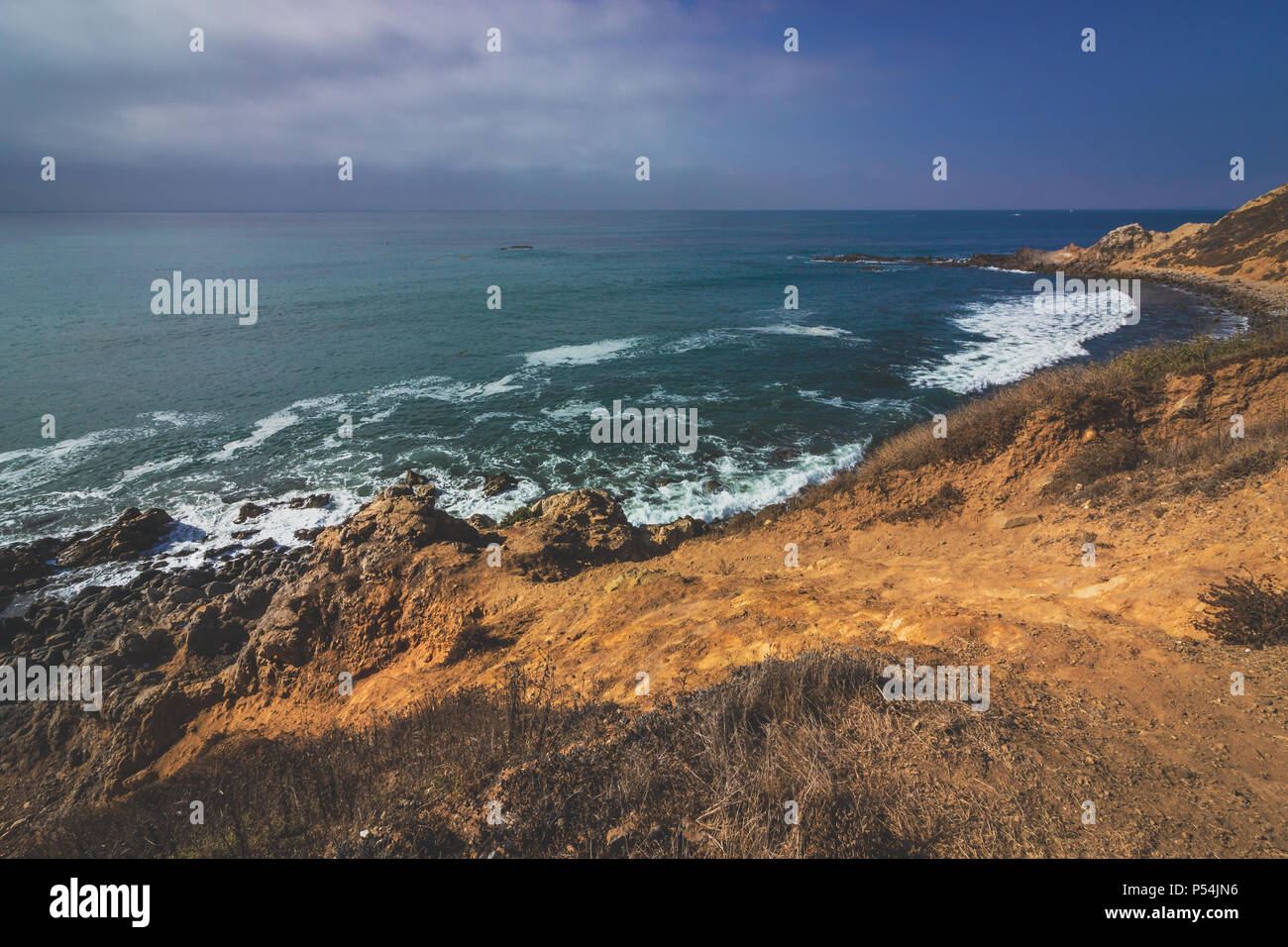Beautiful waves crashing onto the rocky beach of Bluff Cove with Flat Rock Point rock formation in the background, Palos Verdes Estates, California - Stock Image