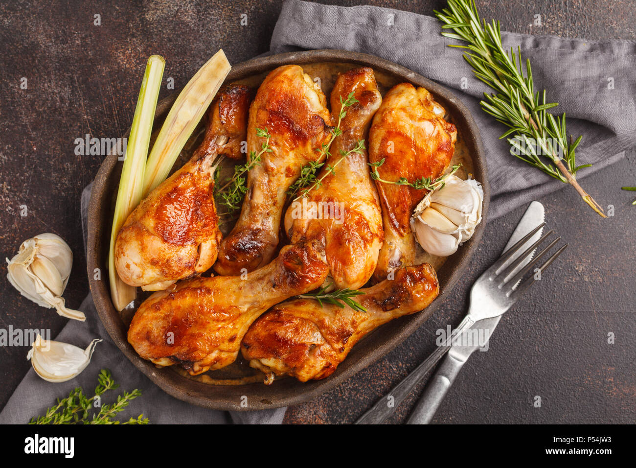 Grilled spicy chicken legs baked with garlic, rosemary and thyme. Top view, dark background. - Stock Image