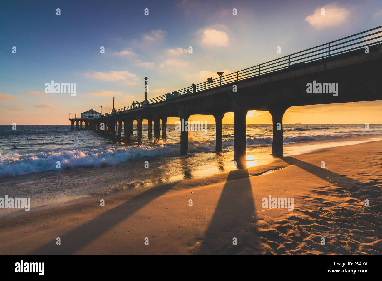 Colorful sky and clouds over Manhattan Beach Pier at sunset with long shadows cast on the beach, Manhattan Beach, California - Stock Image