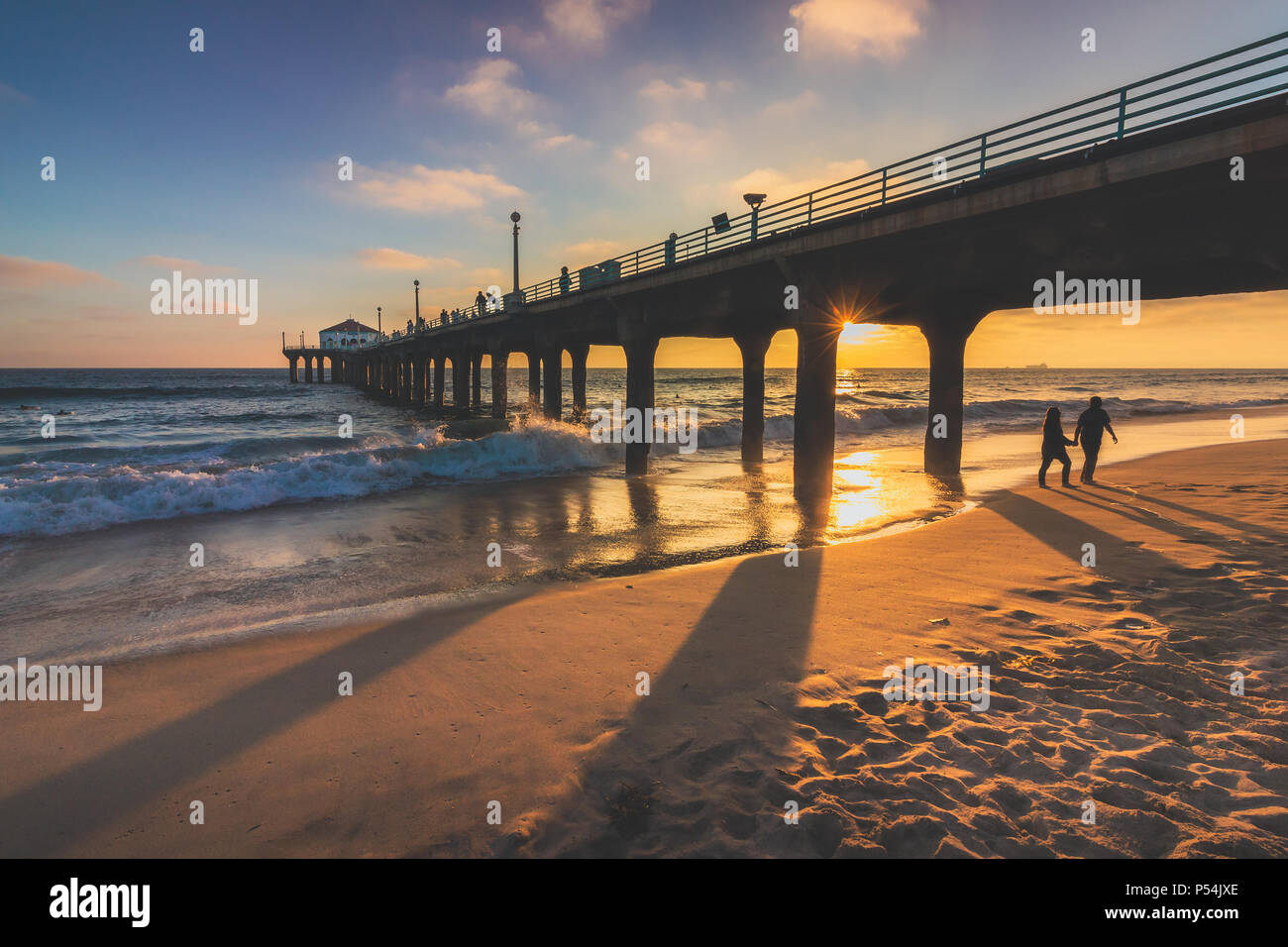 Couple walking under the Manhattan Beach Pier at sunset with long shadows cast on the beach, Manhattan Beach, California - Stock Image