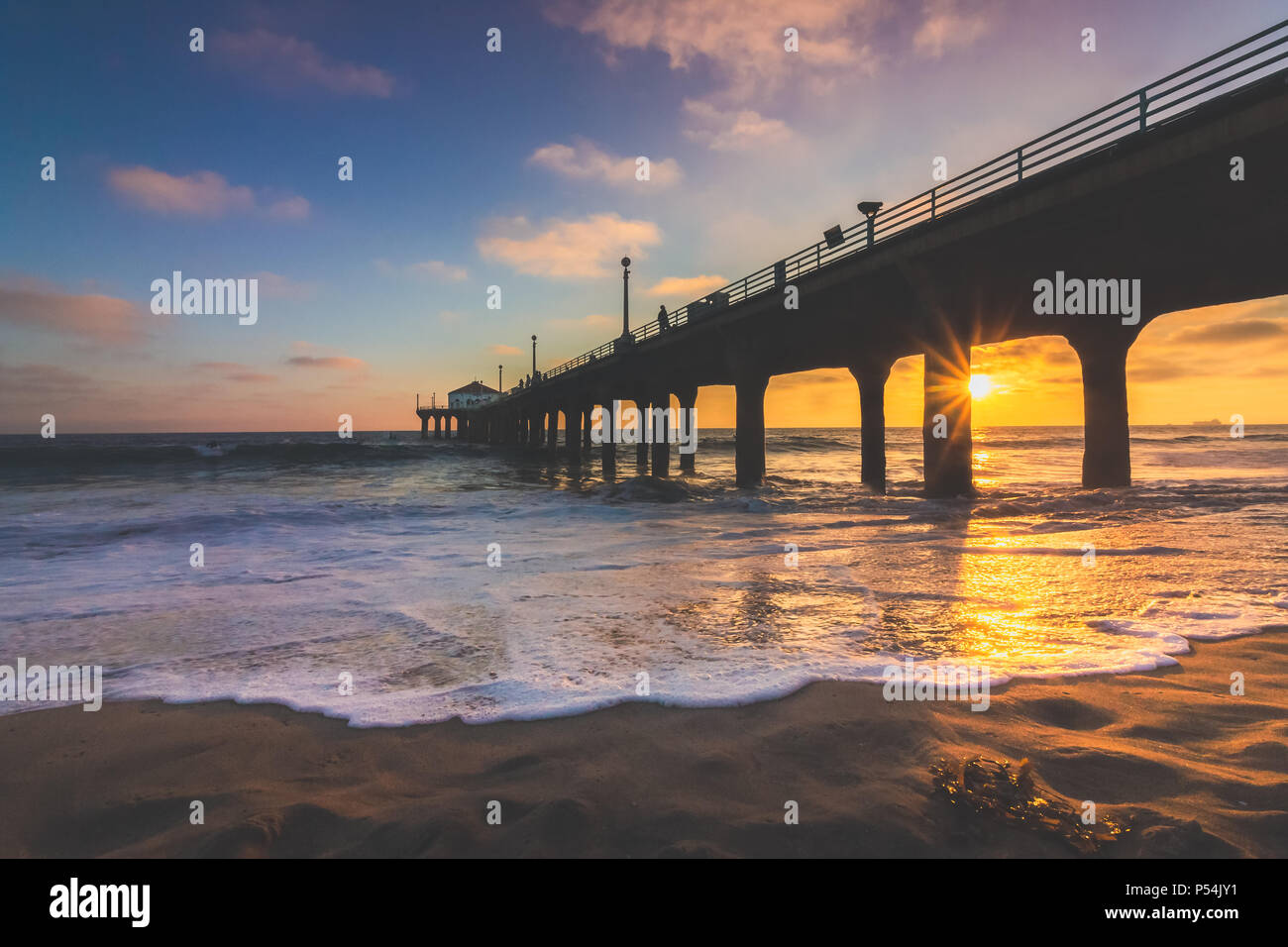 Colorful sky and clouds over Manhattan Beach Pier at sunset with smooth waves washing onto the beach, Manhattan Beach, California - Stock Image