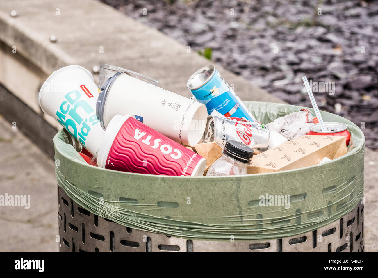 A street litter bin full of cans, plastic cups and packaging, England, UK - Stock Image