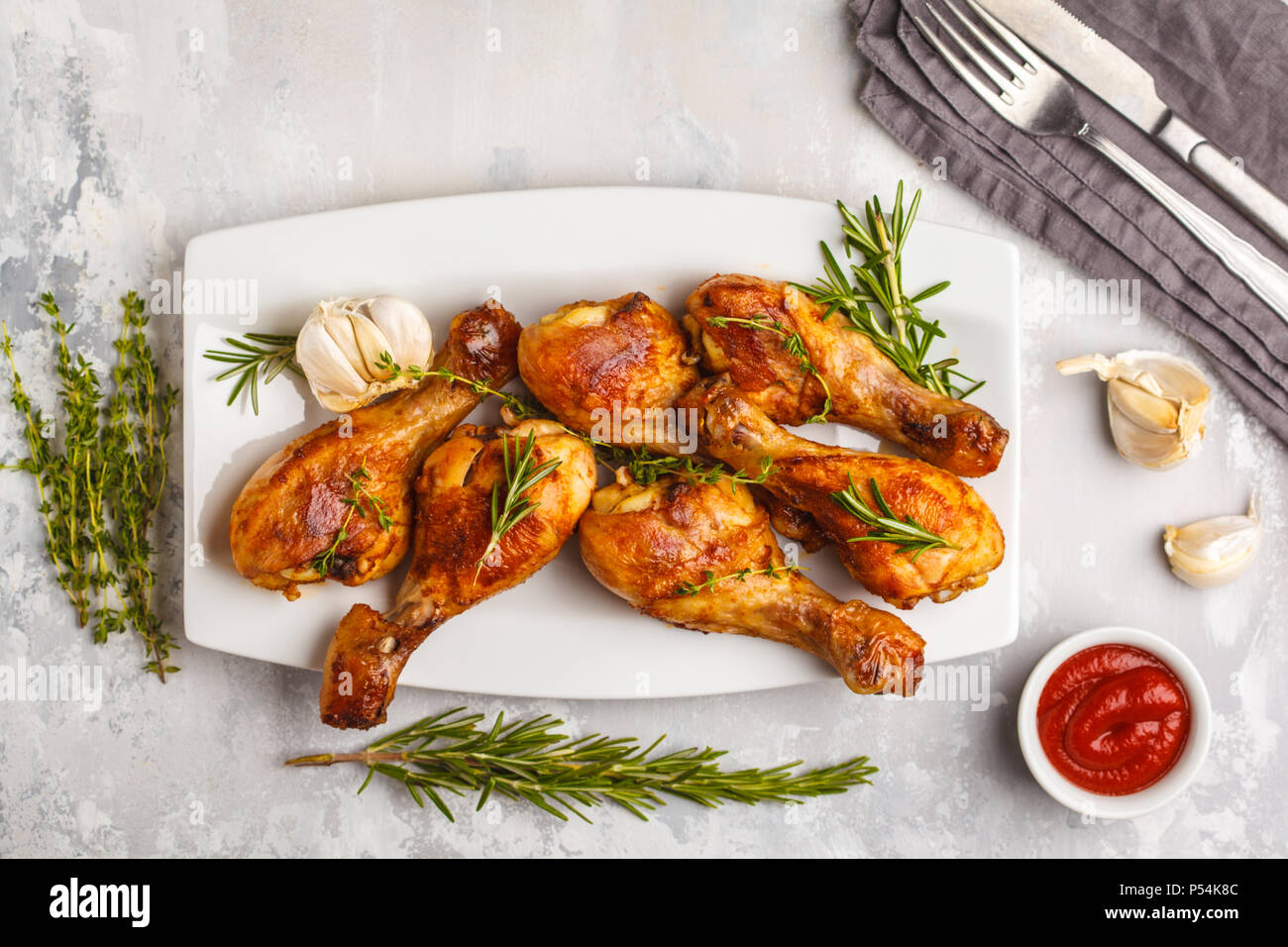 Grilled spicy chicken legs baked with garlic, rosemary and thyme in white dish on white background. - Stock Image