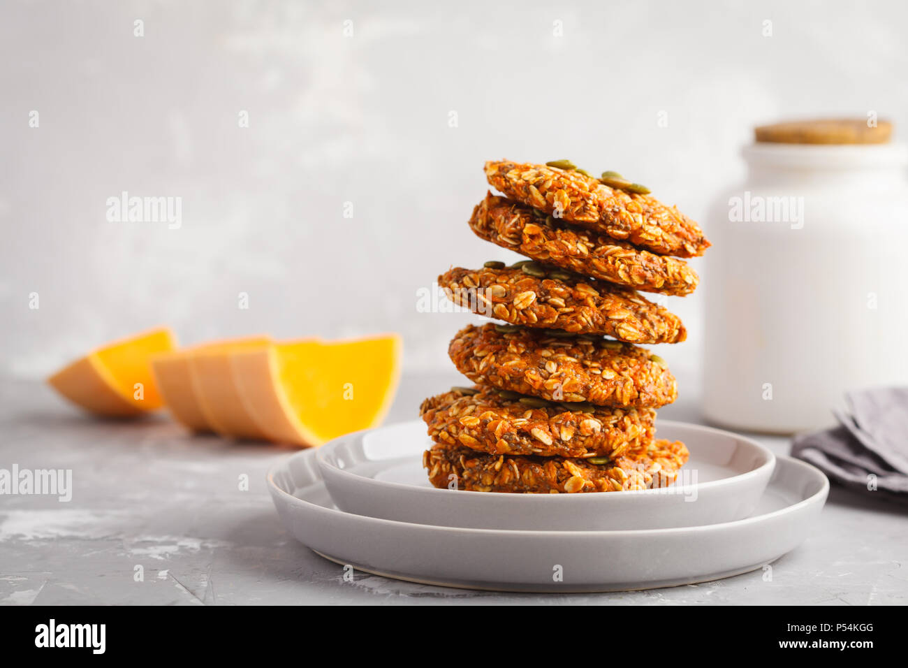 Stack of natural oatmeal pumpkin cookies on a gray plate, halloween food, vegan food concept. Stock Photo