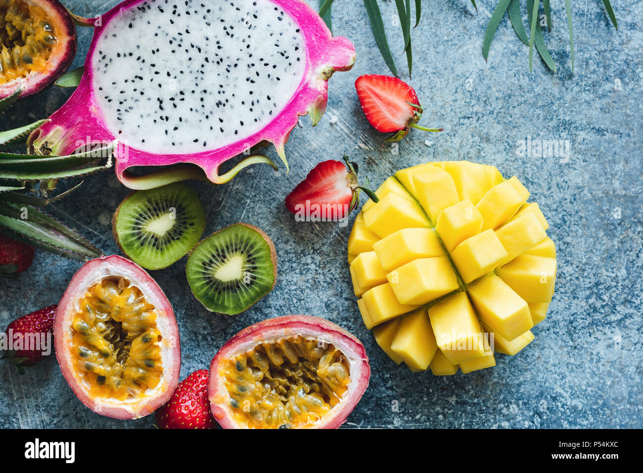 Mango, pitaya, kiwi, strawberry and passion fruit. Tropical fruits on concrete background - Stock Image