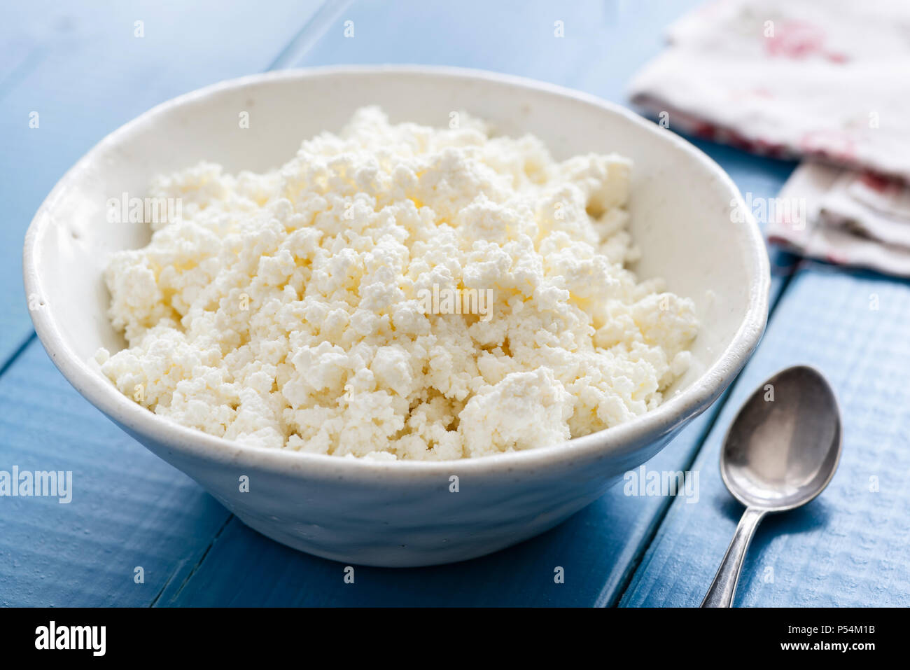 Ricotta or cottage cheese in white bowl on blue table. Healthy dairy product. Tvorog or farmer's cheese. - Stock Image