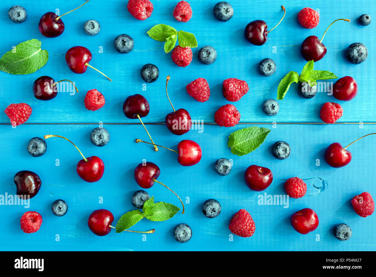 Berries on blue background, flat lay. Berry pattern on blue wood background. Raspberry, sweet cherry, blueberry and mint leaf pattern - Stock Image